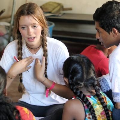 Een vrijwilliger doet werk binnen de gemeenschaps in Sri Lanka in een groep, en leert jonge kinderen Engelse zinnen.